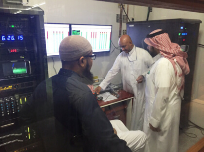 Control Room with three men implementing the Muslim American invention which will provide automatic translation services to people in Mecca.