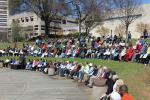 Over 200 people sit outdoors at the park to listen to words of peace and togetherness being spoken.