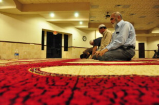 A few men pray together in a large, quiet room.