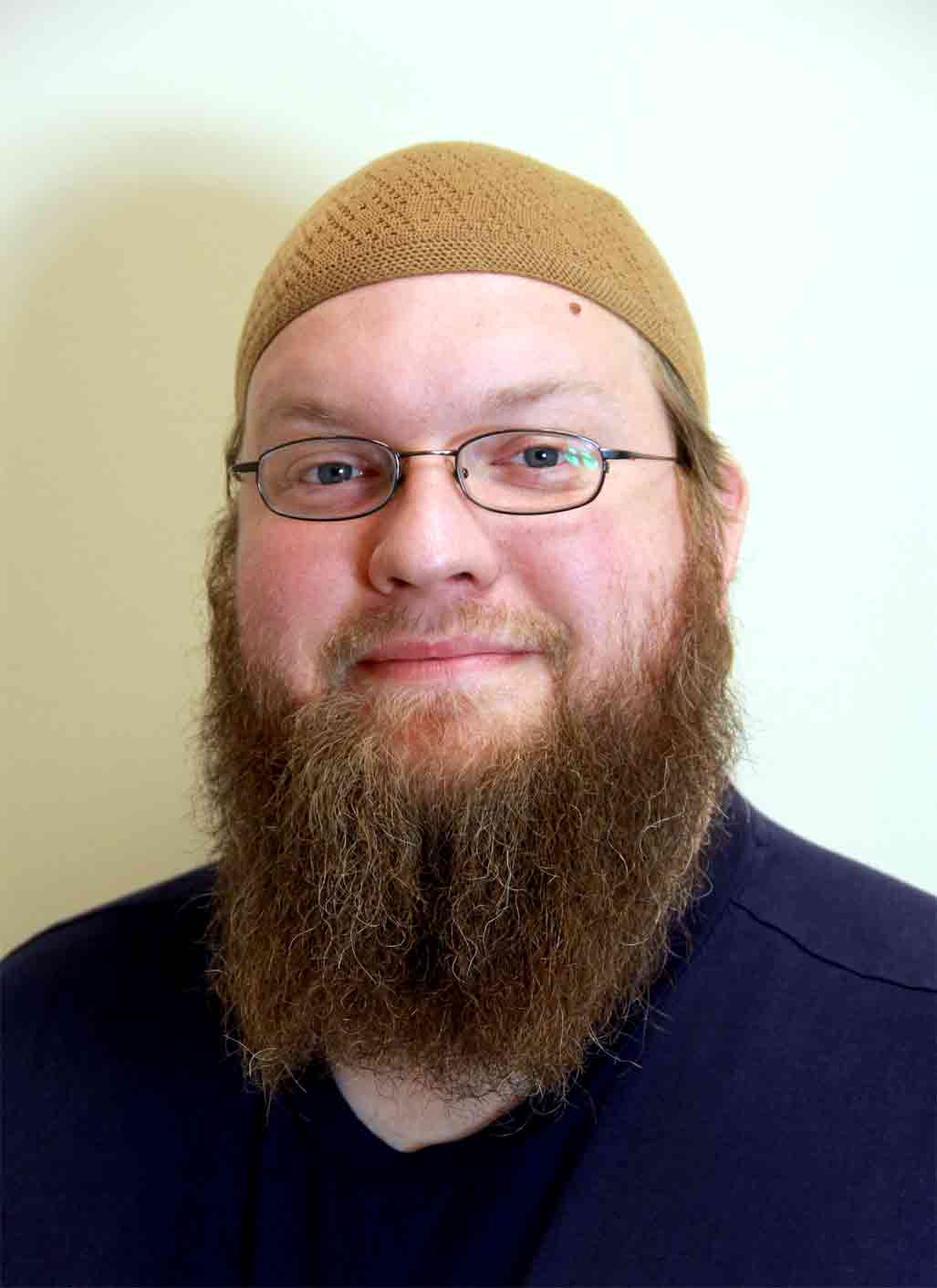 Duston Barto, an advocate for religious liberty and civil rights, pictured here with long beard and brown kufi cap.