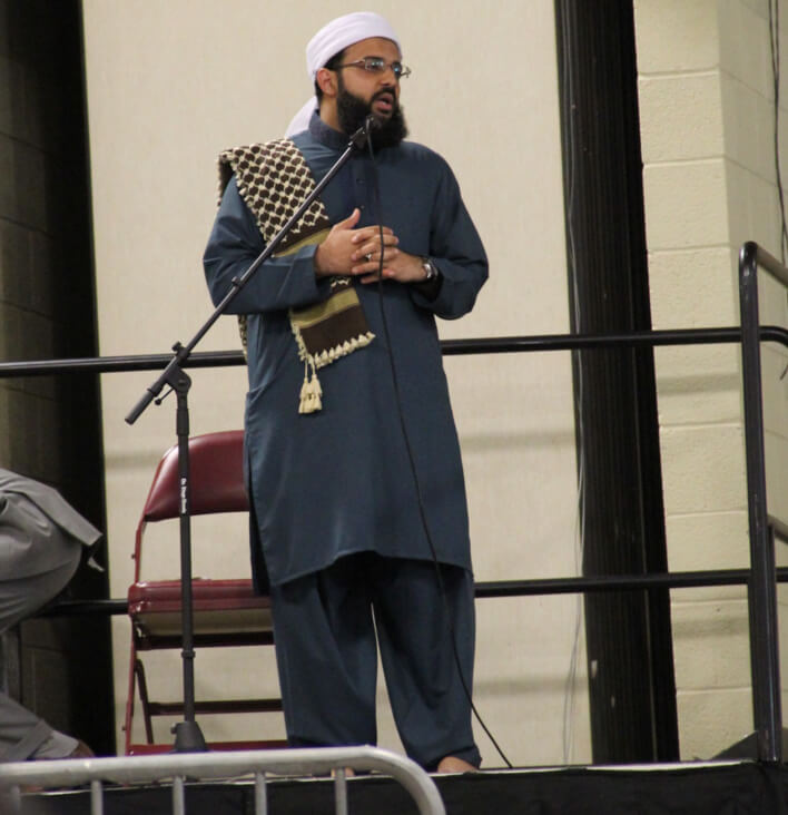 Imam Atif Chaudhry of the Islamic Center of Greater Charlotte stands to delver a lecture to the united worshipers.