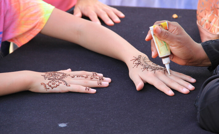 Henna is applied to a young girl's hand during Eid.