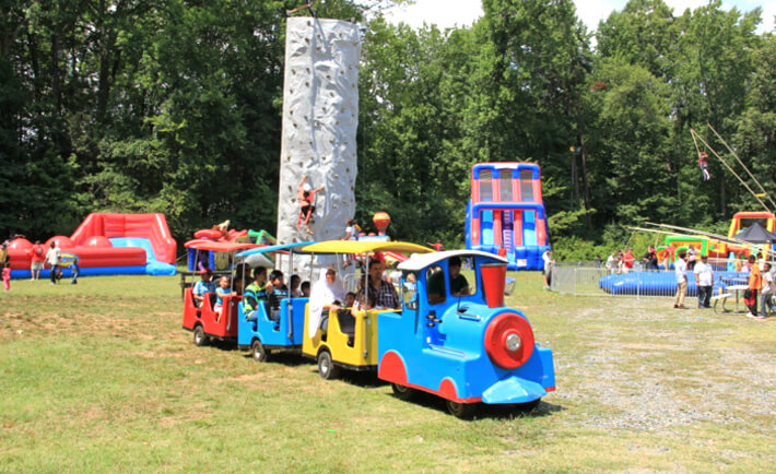 A colorful train carries kids of all ages through a carnival playground at ISGC that was created for celebrating a united Eid festival.