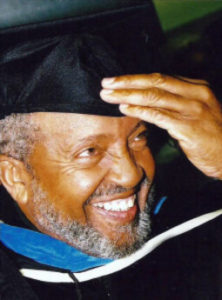 Imam Mohammed grins excitedly as he receives his PhD after many years of study.
