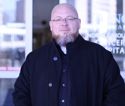 Imam Shane Atkinson stands outside of UNC Chapel Hill hospital doors where he is an active chaplain.