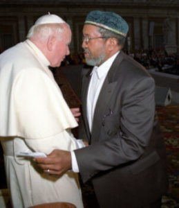 Imam W. D. Mohammed shakes hands with Pope John Paul II and holds his arm while speaking to the pontiff.