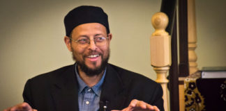 Imam Zaid Shakir laughs and uses his hands to express what he is saying.