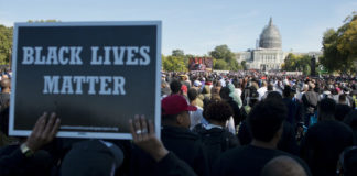 "At the Justice Or Else rally, a sign is held up reading ""Black Lives Matter"" while a crowd of hundreds of thousands stretch between the foreground and the capitol building in the distance. Minister Farrakhan appears on a large screen."