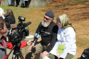 A Muslim couple is interviewed by several cameras representing different media outlets at the park.