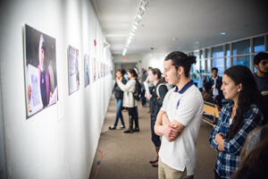 People look at photographs displayed brightly illuminated on the gallery wall.