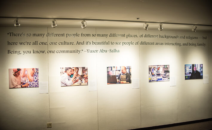 """Photographs of Muslims in the community are displayed on a wall and accompanied by a quote by Yusor Abu-Salha that reads """"There's so many different people from so many different places, of different backgrounds and religions - but here we're all one, one culture. And it's beautiful to see people of different areas interacting, and being family. Being, you know, one community."""""""