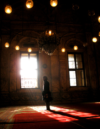A person stands alone near the light of a window in a large, high-vaulted room with large, softly-lit lanterns suspended overhead.