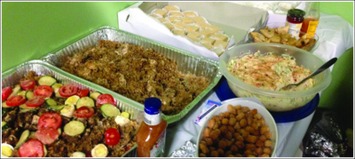 Traditional Mediterranean food spreads across a table for the gathered members of the community.