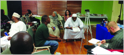Imam Yahyah sits in the foreground clarifying points for audience members, a fellow presenter and Imam sit opposite from him in the background.