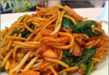 Noodles are piled high on a plate with bright and colorful vegetables and succulent pieces of chicken.