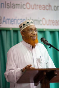 handsome African American man smiles as he speaks during a Dawah conference
