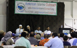 Four Imams sit on stage during a dawah conference while an audience asks questions