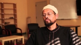 Imam Zaid speaks and sits in the sunlight indoors.