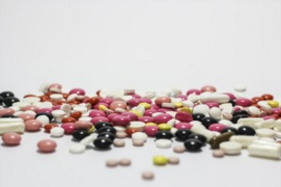 Several different colors of prescription pills are spilled.