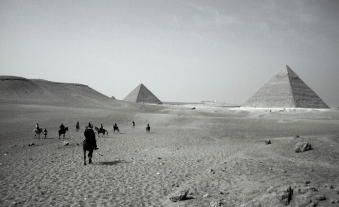 vintage image of the pyramids of Giza with a small caravan