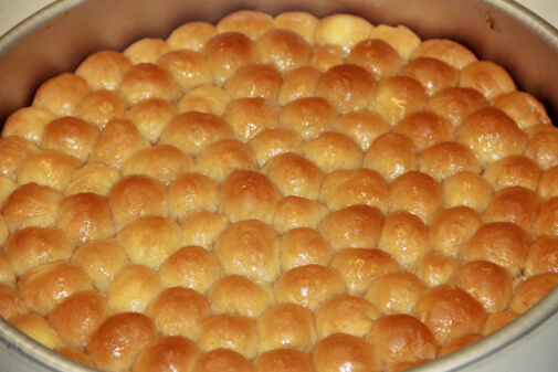 Golden honeycomb bread sits in a pan.