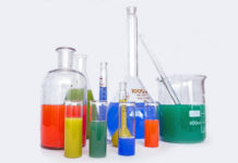 Beakers of unappealing liquid are gathered in front of a white background.