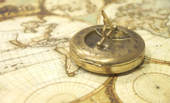 antique compass with miniature sextant sits atop an old world map.