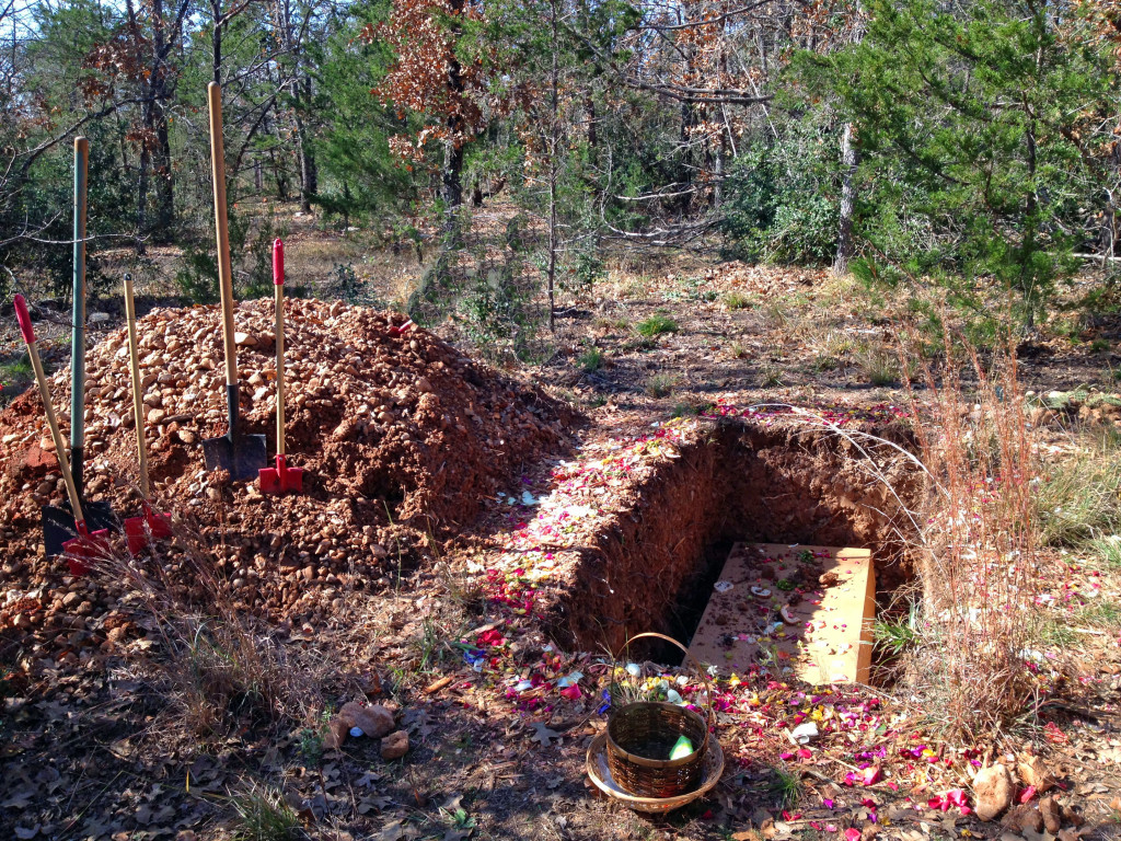 A Green Burial shown here with a natural forest setting and a simple pine box coffin which will break down over time.